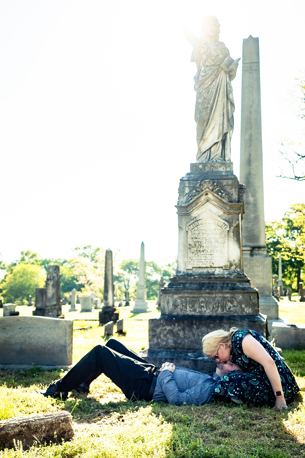 Cute couple share a kiss at the base of a headstone at Mt. Olivet Cemetery