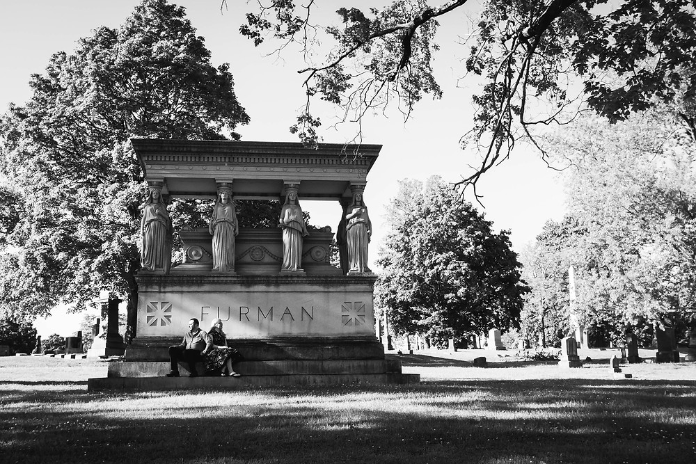 Black and white cute couple seated on mausoleum at Mt. Olivet Cemetery