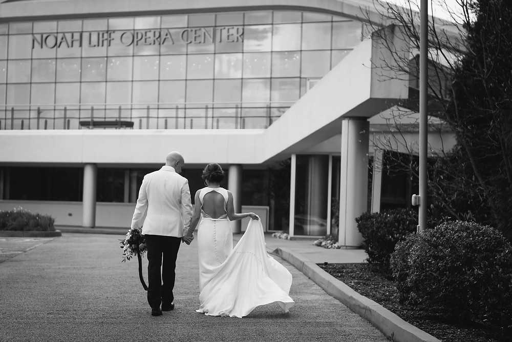 Black and white bride and groom walk back to wedding at Noah Liff Opera Center