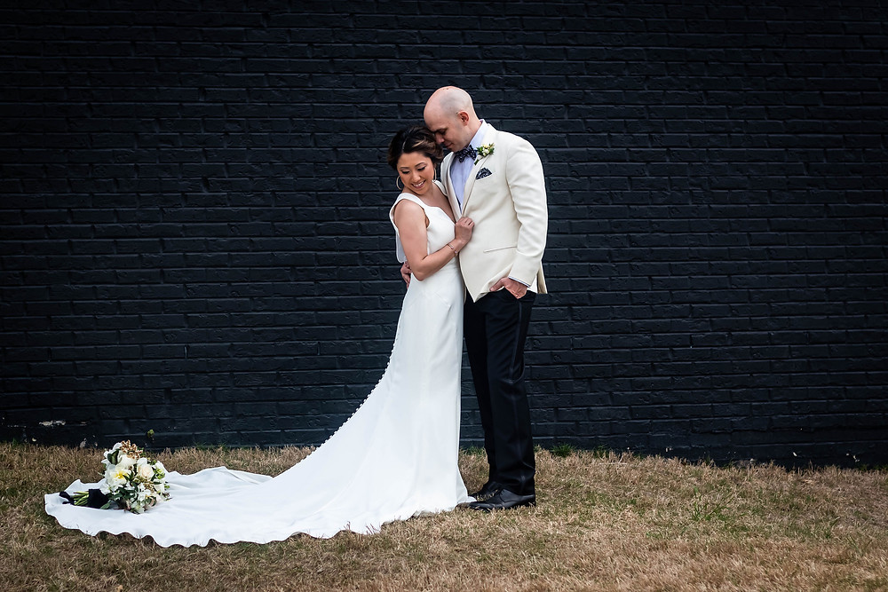 Bride and groom snuggling against black wall at Noah Liff Opera Center