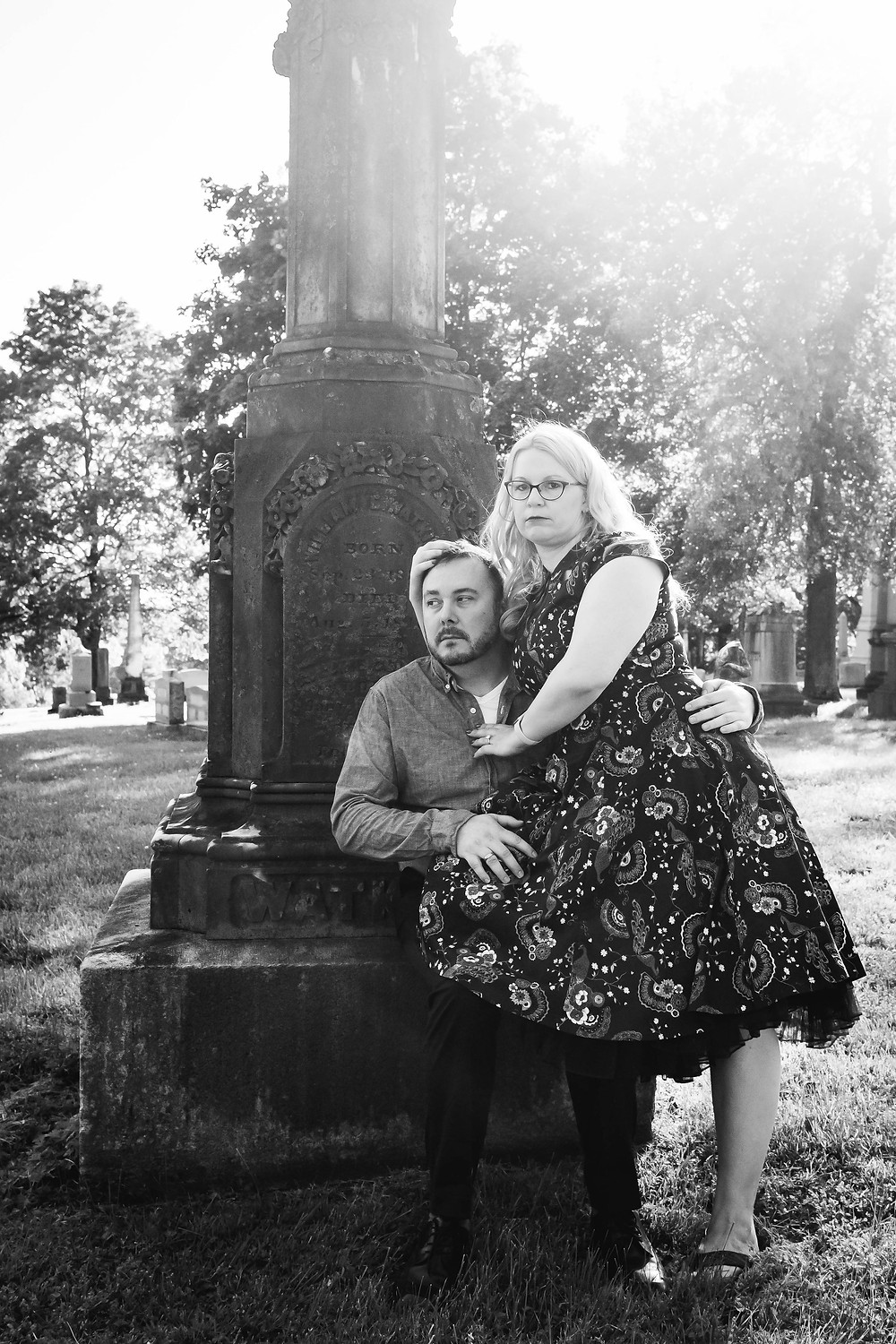 Black and white vogue couple pose on headstone at Mt. Olivet Cemetery