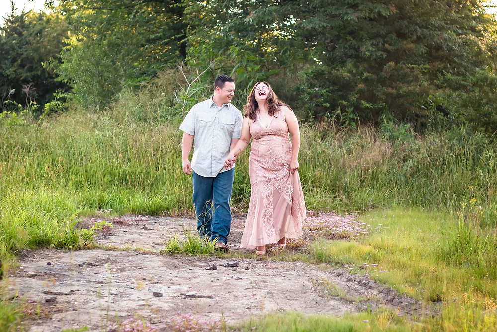 Cute couple walk through a field laughing in Lewisburg, Tennessee