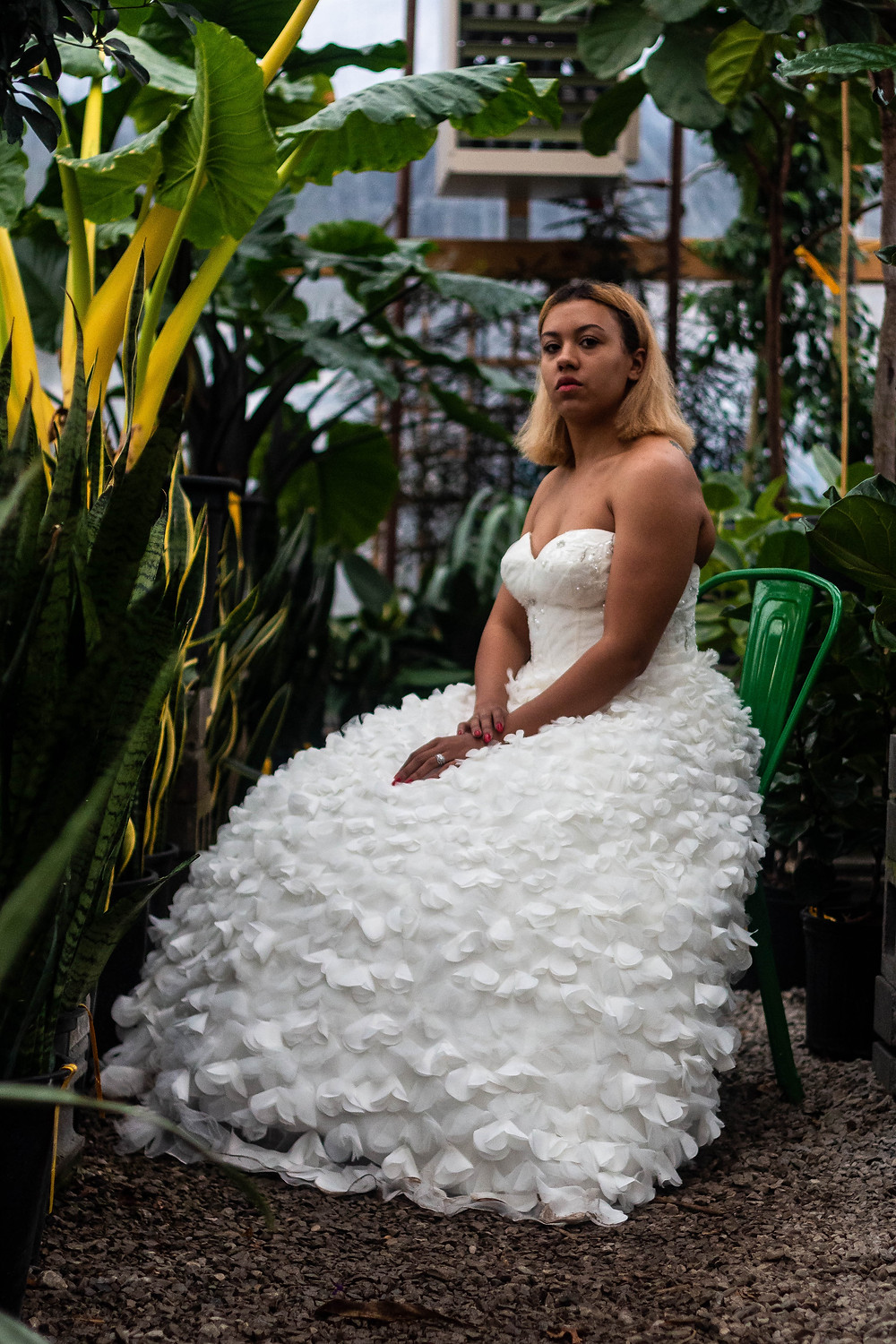 Vogue bride sits in greenhouse with wedding dress