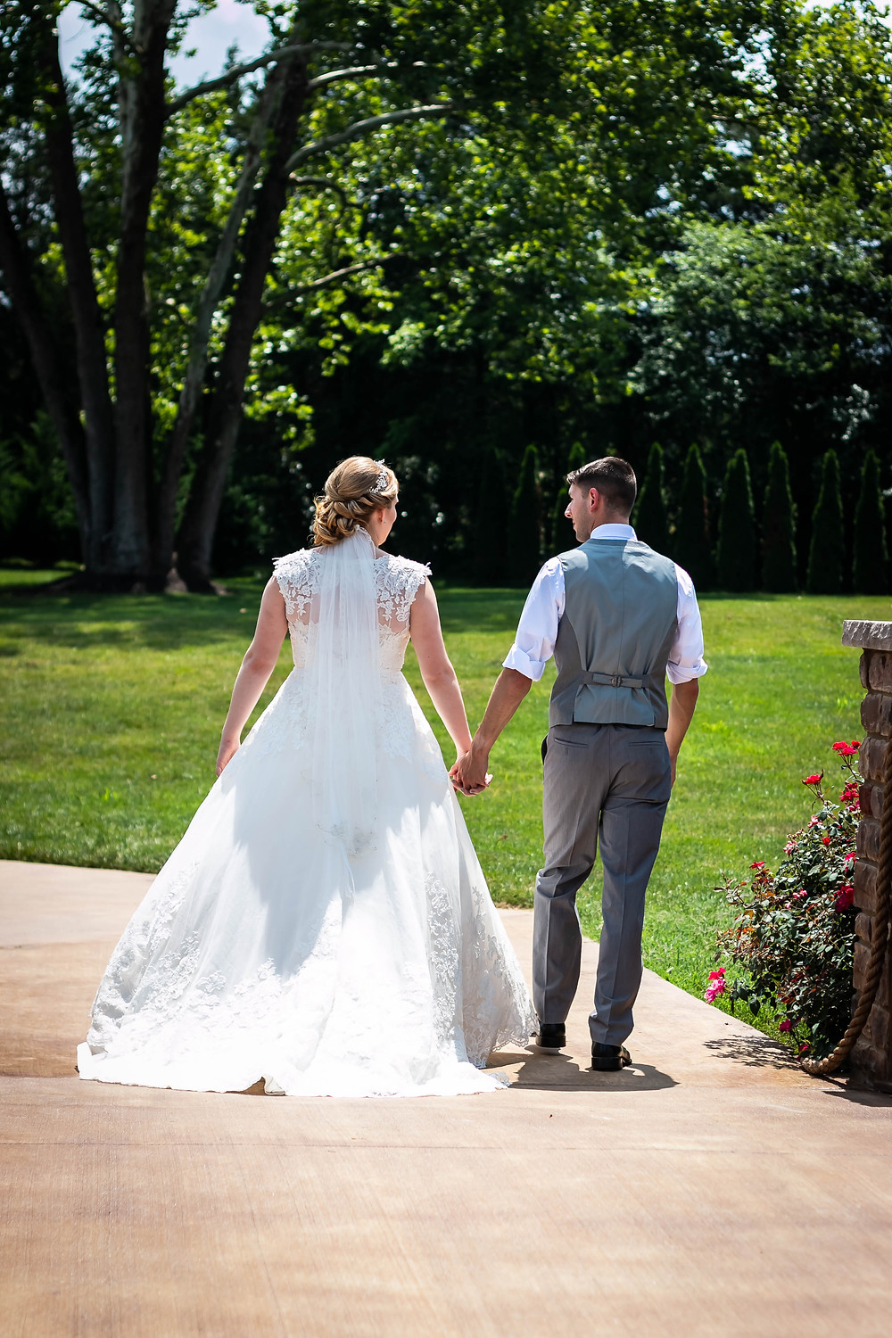 Bride and groom walking on path at Sycamore Farm