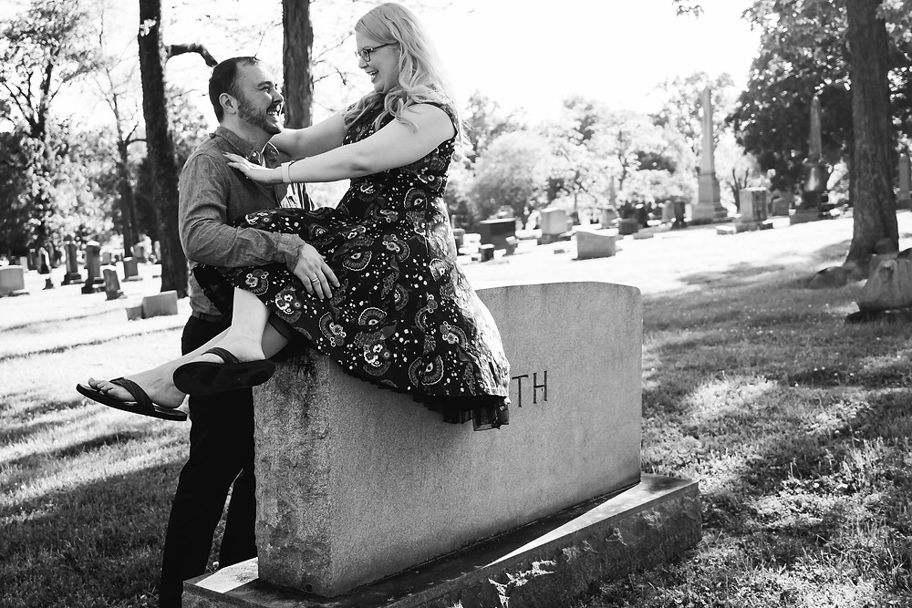 Black and white cute couple share a laugh on a headstone at Mt. Olivet Cemetery