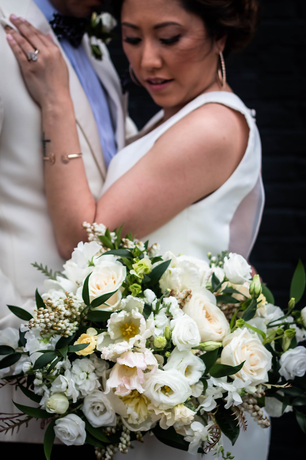 Detail shot of bridal bouquet with bride and groom in background at Noah Liff Opera Center