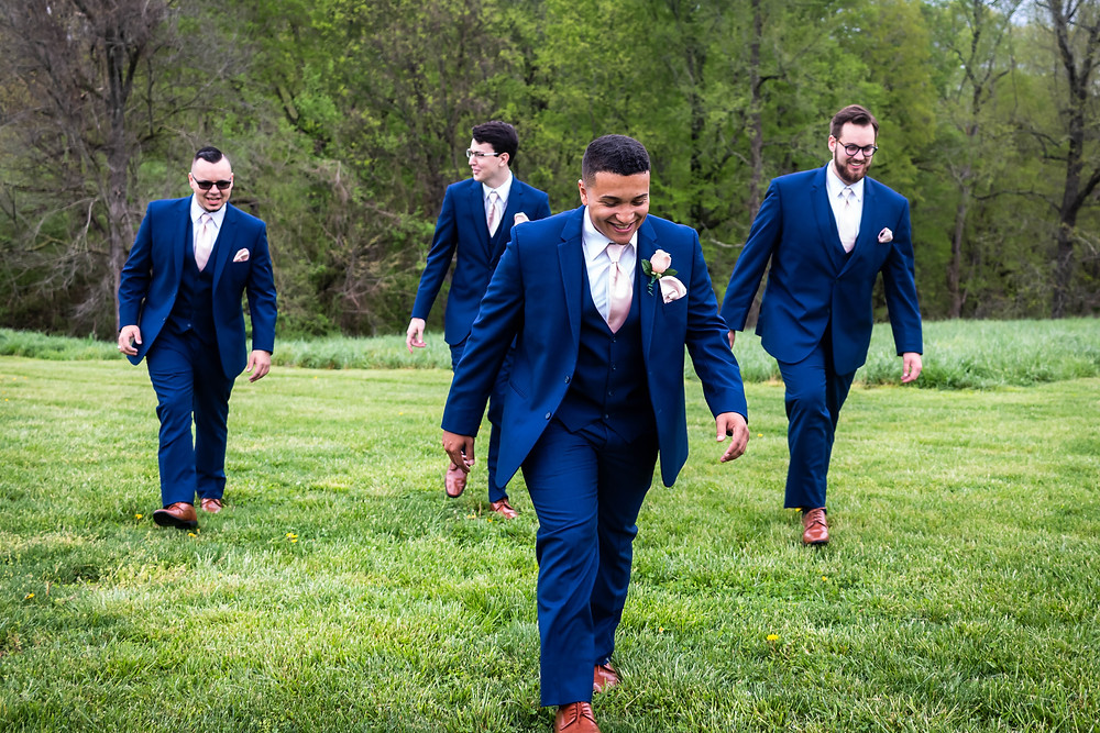 Grooms walking in field at Owen Farm