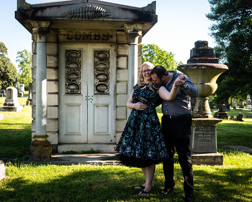 Cute couple share a kiss in front of a mausoleum at Mt. Olivet Cemetery