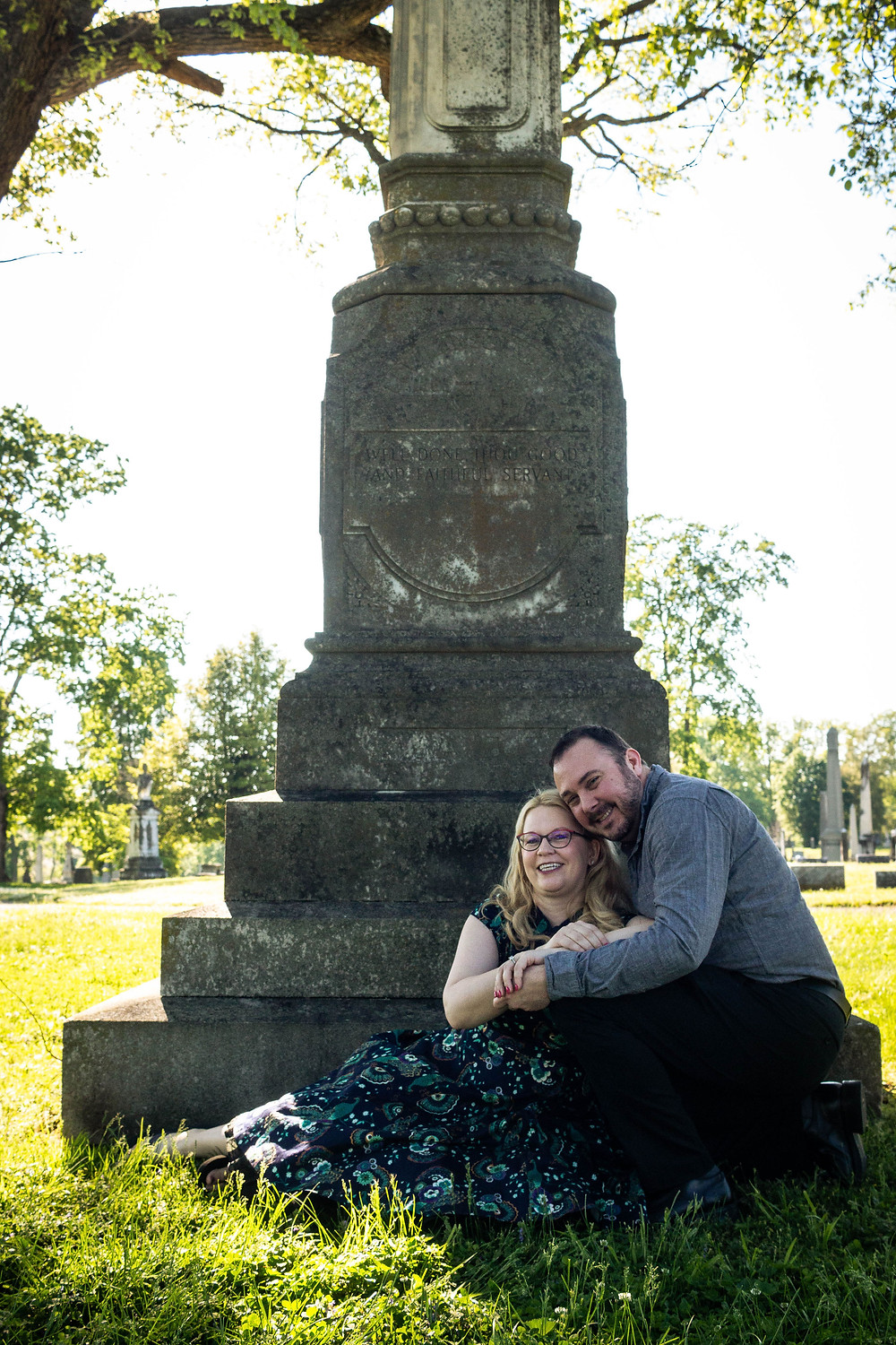 Cute couple sitting at the base of headstone at Mt. Olivet Cemetery
