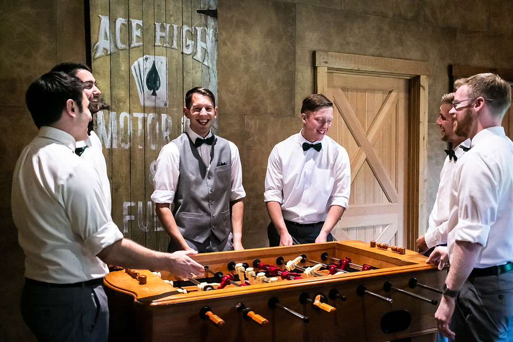Groom and groomsmen playing foosball at Sycamore Farm