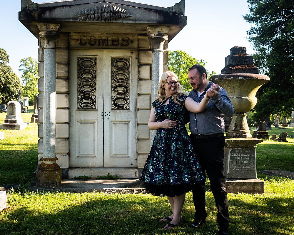Cute couple pose in front of a mausoleum at Mt. Olivet Cemetery