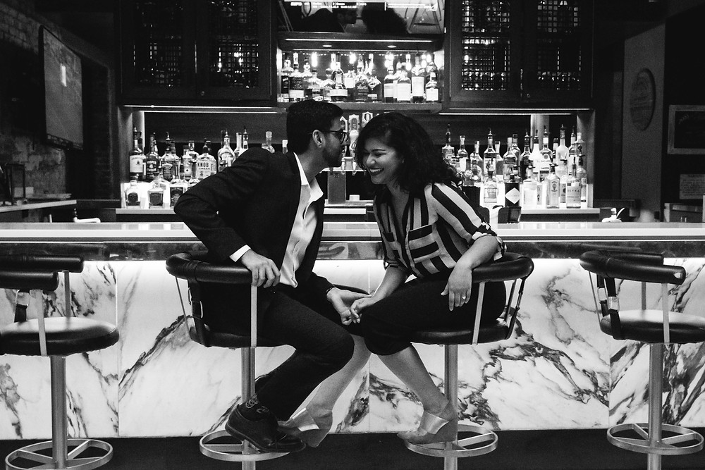 Black and white cute couple share a secret at a bar at Union Station Hotel