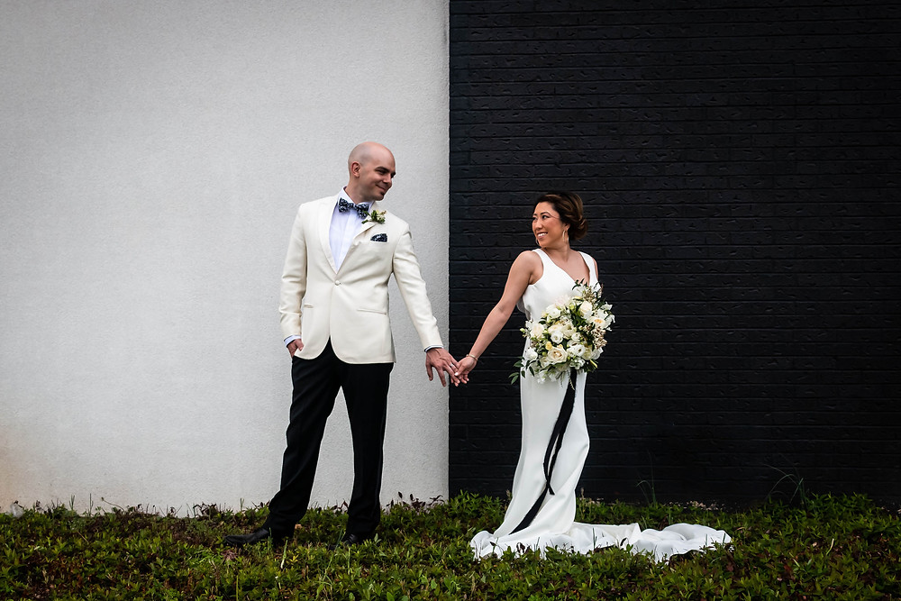 Bride and groom holding hands against black and white wall at Noah Liff Opera Center
