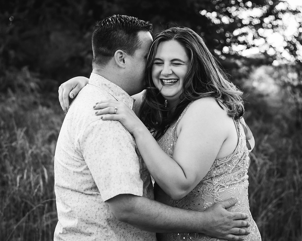 Black and white cute couple share a laugh in a field in Lewisburg, Tennessee