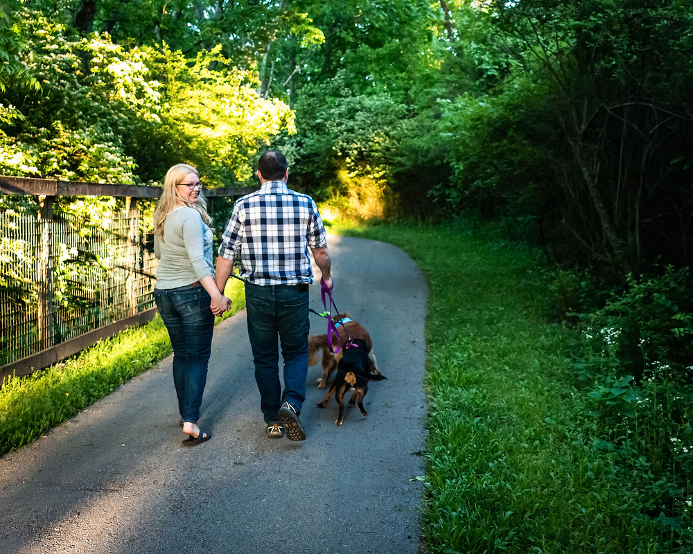 Cute couple walks down a path with dogs at the Nashville Greenway
