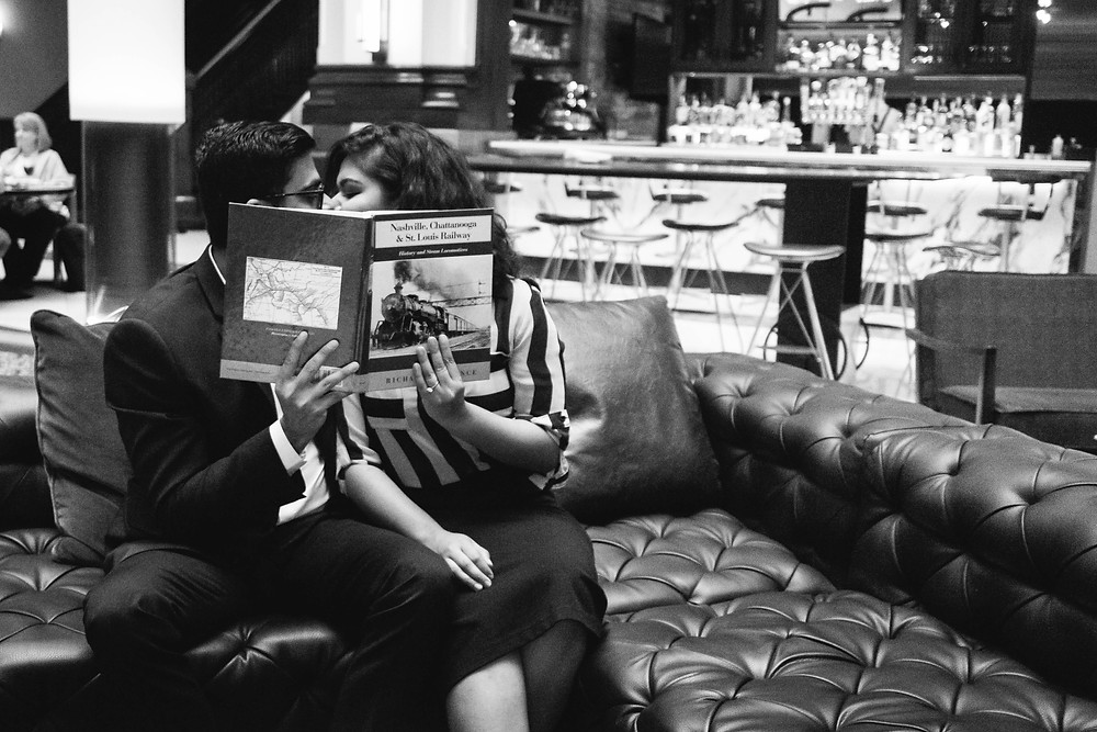 Cute couple share a secret kiss behind a book at Union Station Hotel