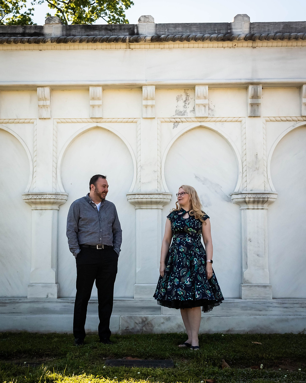 Cute couple stands in front of mausoleum at Mt. Olivet Cemetery