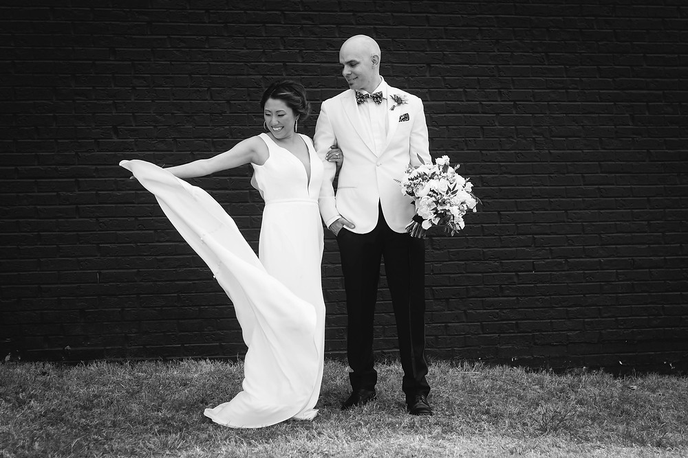 Black and white bride and groom play with wedding dress in wind at Noah Liff Opera Center