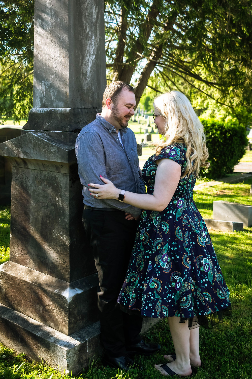 Cute couple lean against a headstone at Mt. Olivet Cemetery