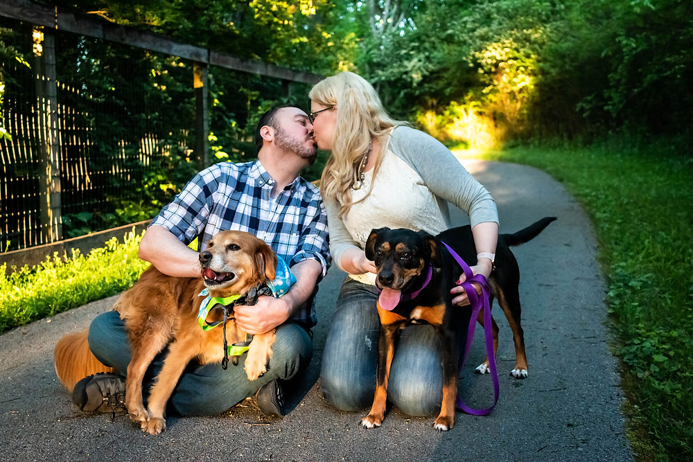 Cute couple share a kiss on path with dogs at the Nashville Greenway