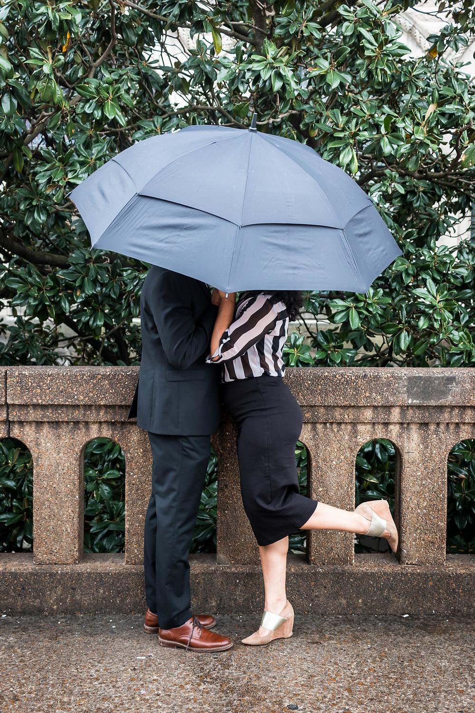 Cute couple shares secret kiss under an umbrella at Union Station Hotel