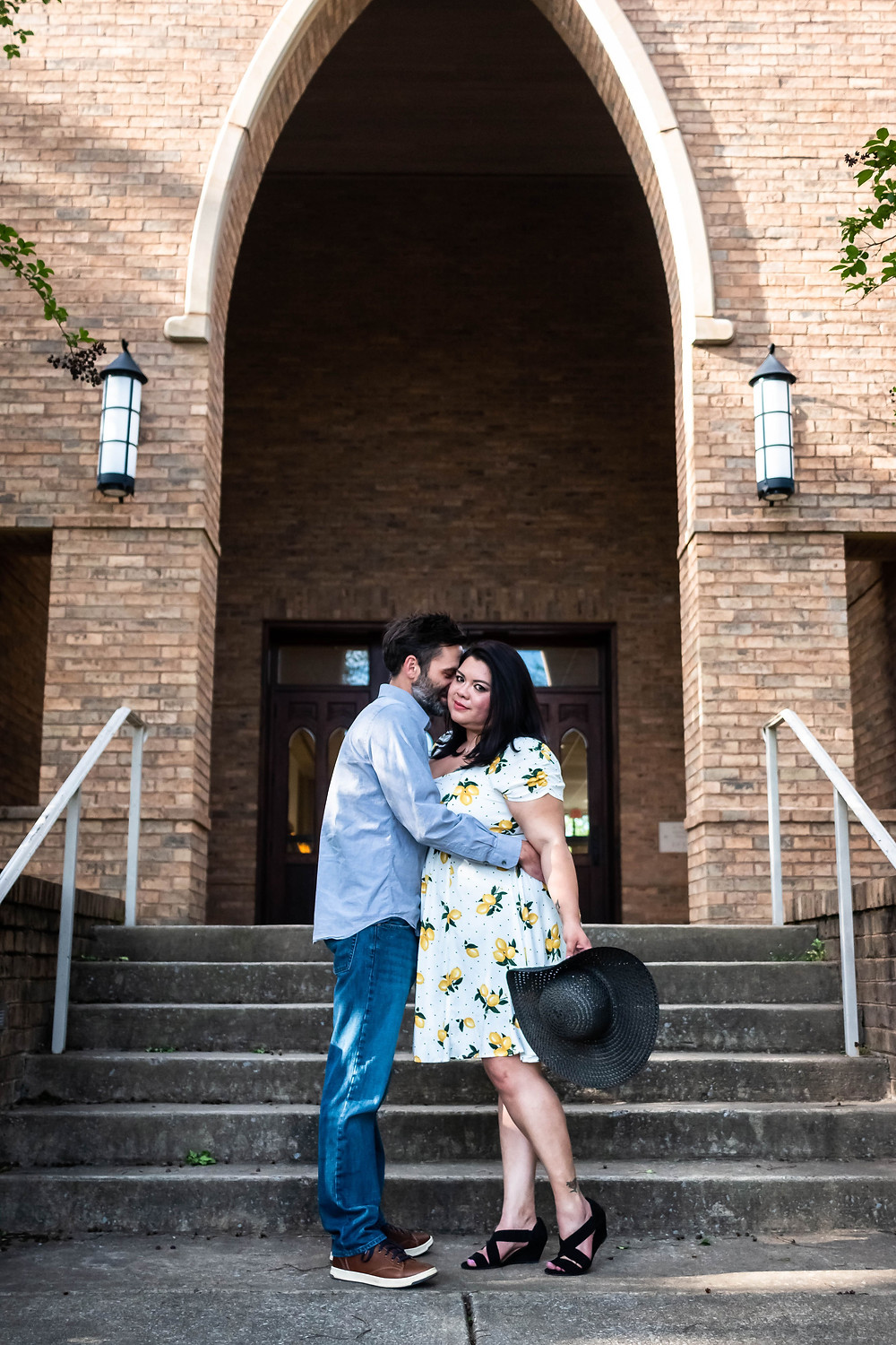 Cute couple share a kiss on steps of historic church in downtown Murfreesboro