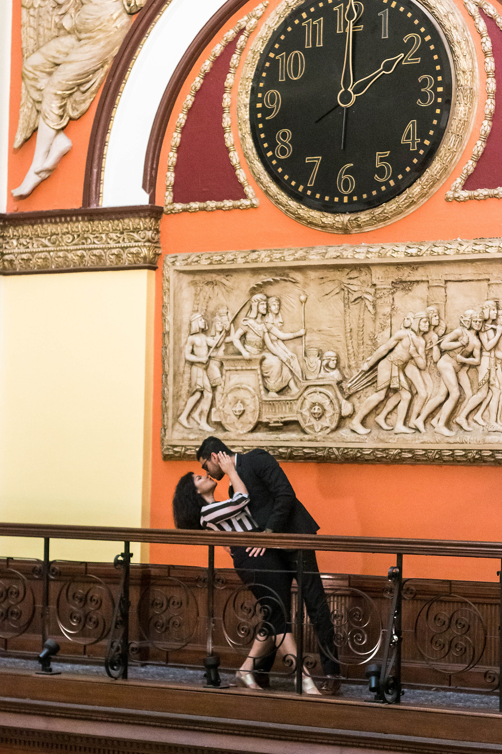 Cute couple share a kiss in front of giant clock at Union Station Hotel