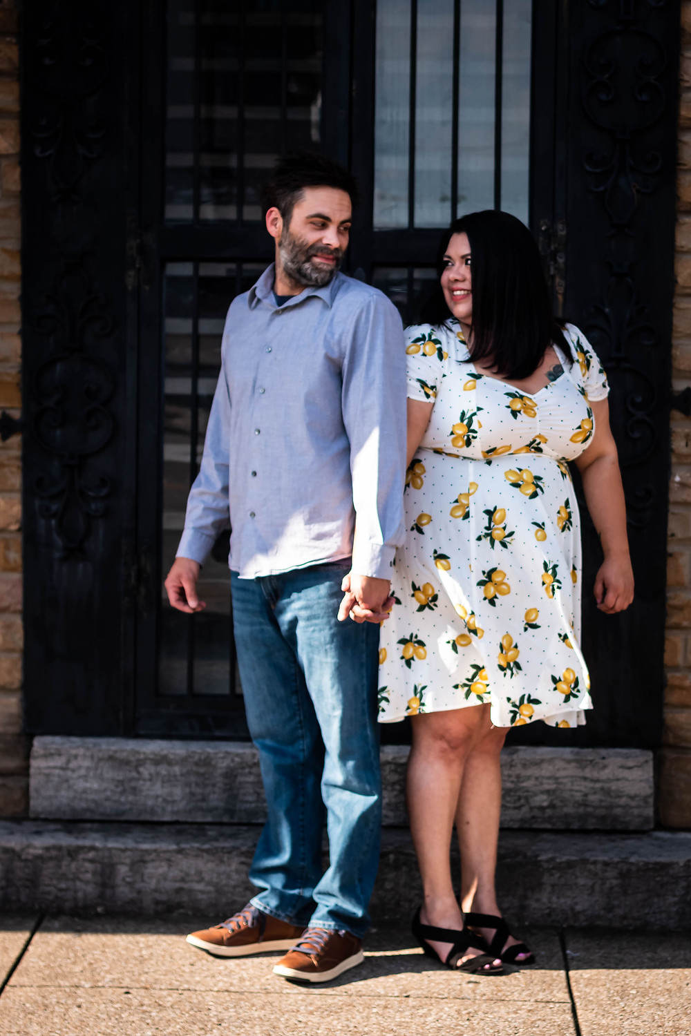 Cute couple holds hands facing back to back in downtown Murfreesboro