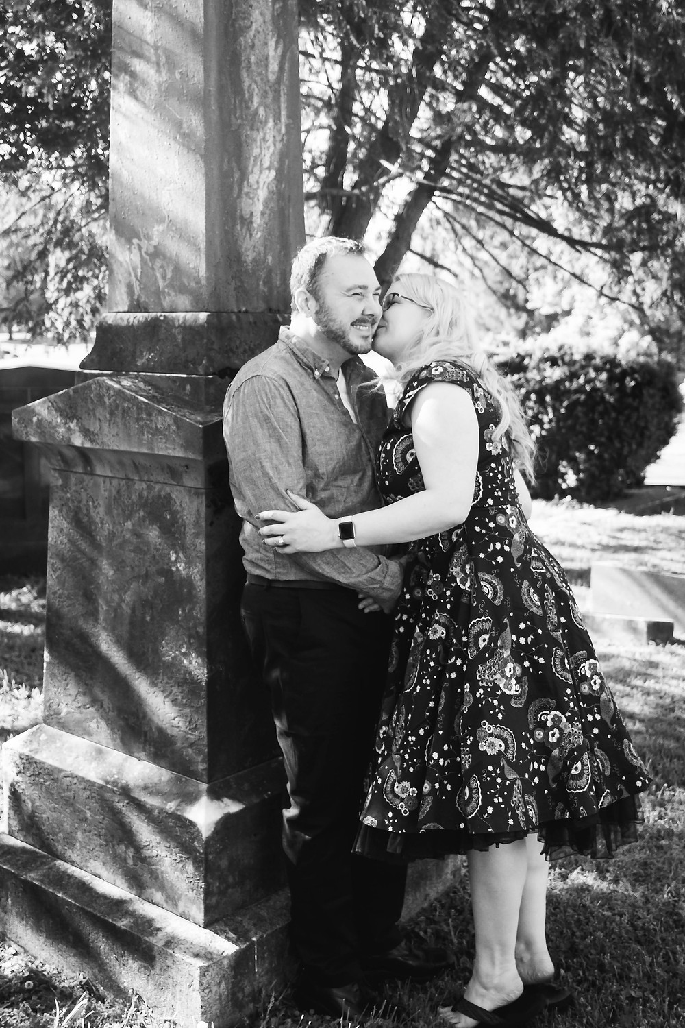Black and white cute couple kiss leaning on a headstone at Mt. Olivet Cemetery