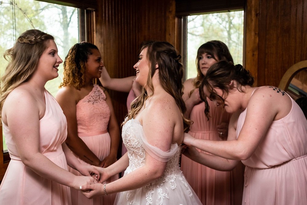 Bride gets dressed surrounded by bridesmaids at Owen Farm