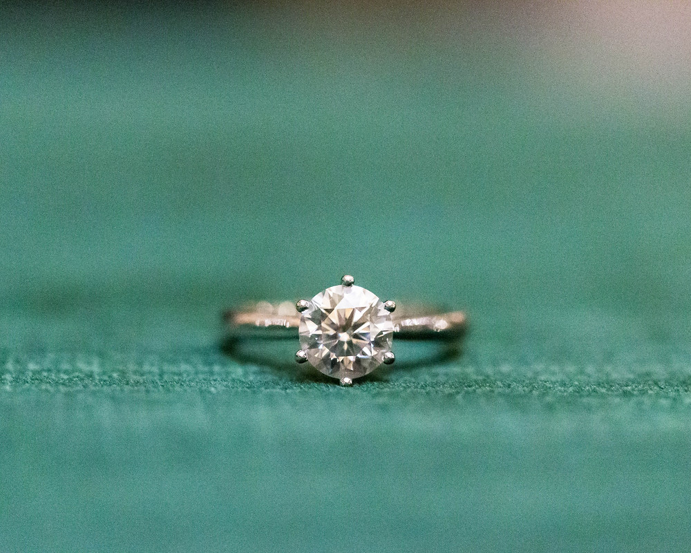 Detail shot of engagement ring against green cushion