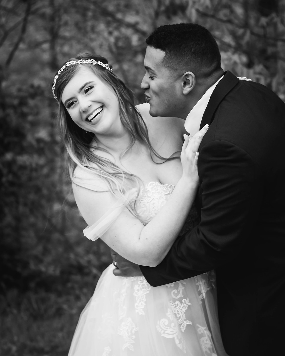 Black and white groom goes in for kiss on the cheek at Owen Farm
