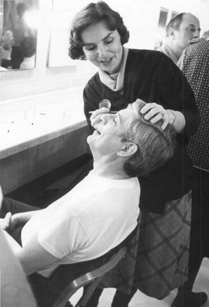 Georgia West applies makeup to an actor in the dressing room