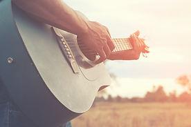 hombre-tocando-guitarra-campo-hierba-dia