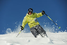 Happy skier dressed in bright yellow spo