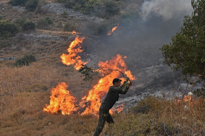 A handout picture released by the official Syrian Arab News Agency (SANA) on September 8, 2020 shows a Syrian man attempting to put off a fire on a hill in Ain Halaqim, in the western countryside of Syria's Hama governorate. (AFP)