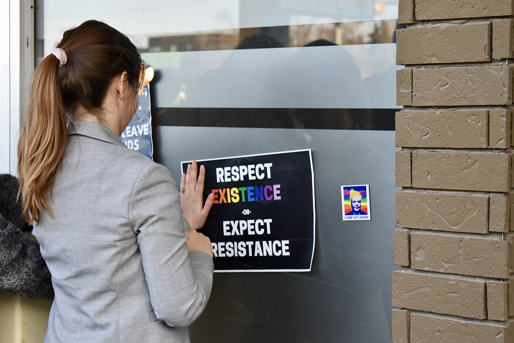 Image of a  young woman putting up a poster which says respect existence or expect resistance