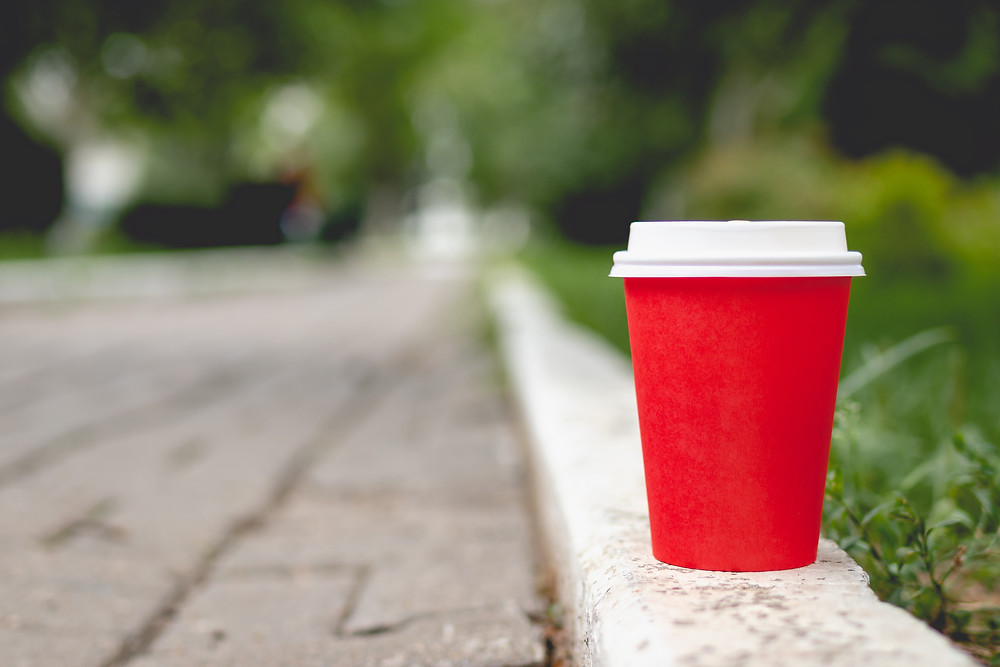 a red disposable coffee cup on the side of a street