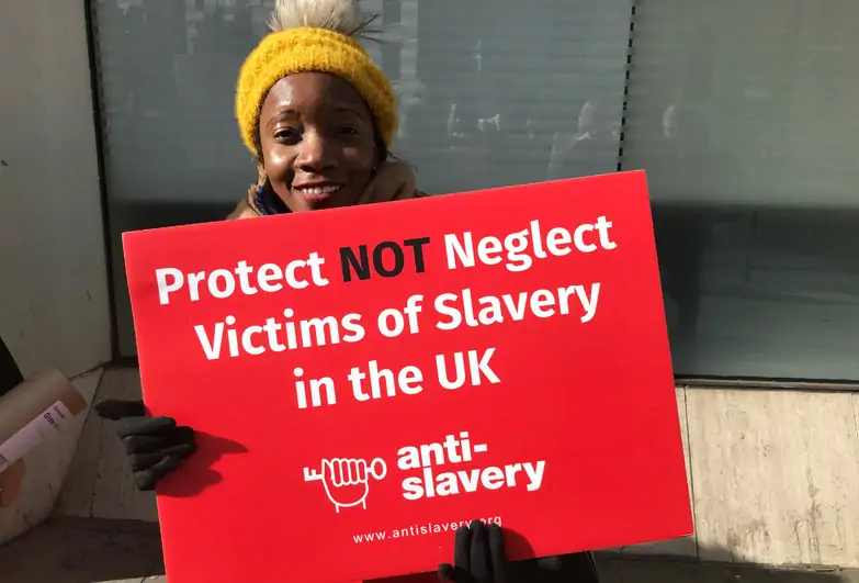 Young person holding a sign against anti slavery