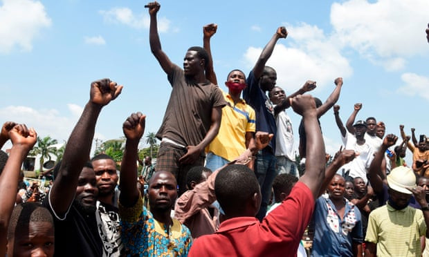 Protesters in Nigeria chant and put their hands in the air to tackle police brutality