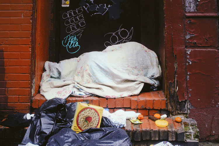 Someone sleeping under a blanket in a doorway.