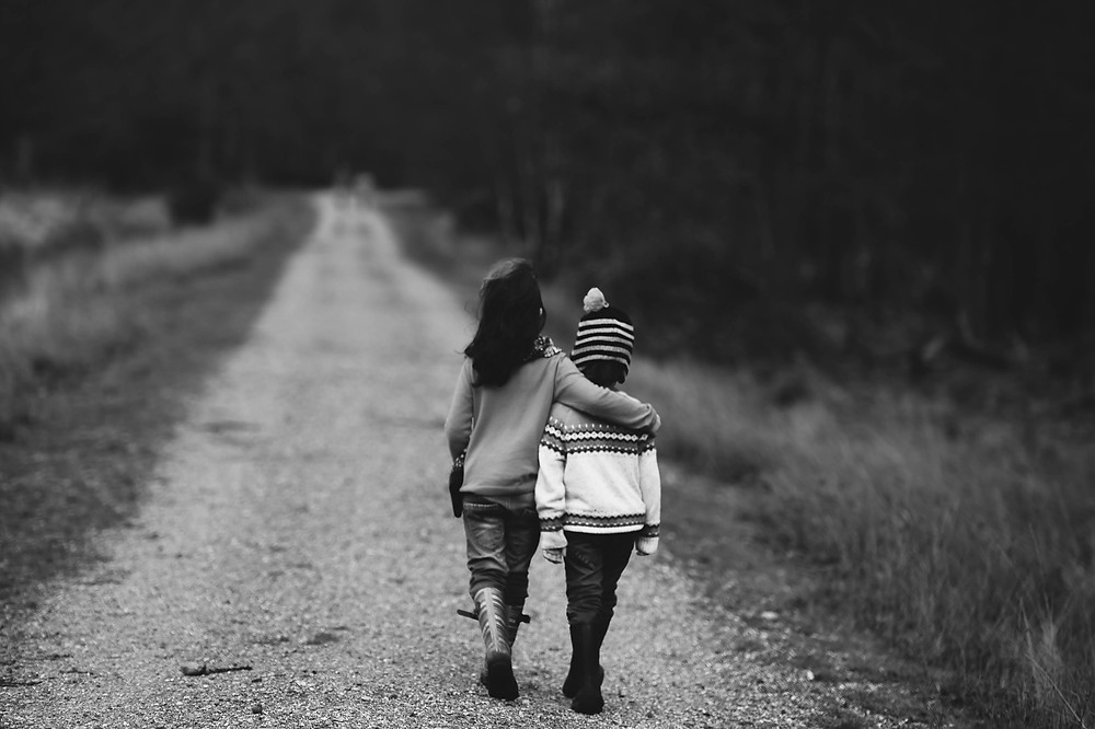 Two children walking away with their arms round each other