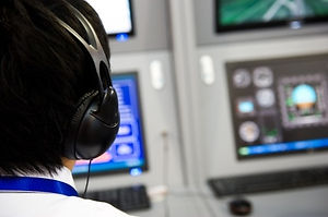 back of the head of an Air Traffic controller wearing headphones and sitting in a test lab