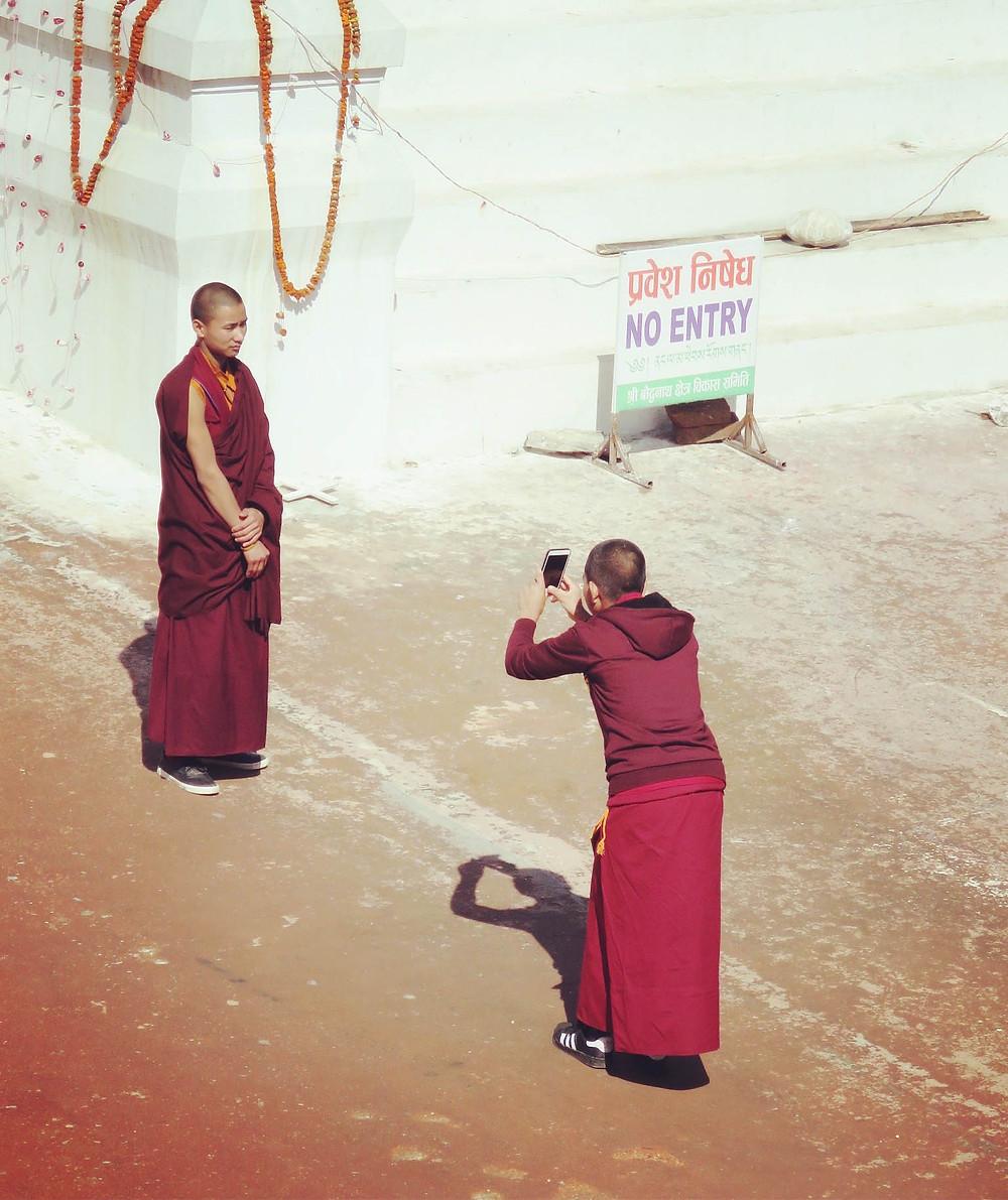 Novice monks take photographs of themselves at Boudinath Stupa, Kathmandu, Nepal