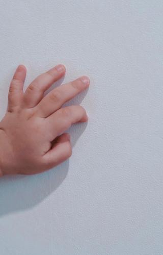 Baby's hand on antiviral wallpaper.jpeg