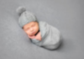 Newborn baby sleeping curled up in grey