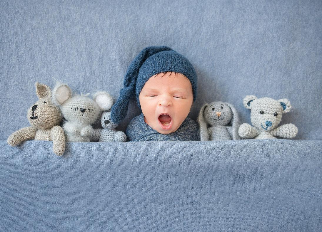 Newborn baby boy yawning and lying betwe
