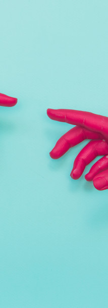 Two painted hands try to reach each othe