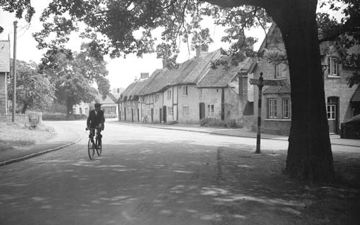 A solitary cyclist makes his way through the village of Monks Kirkby 1953
