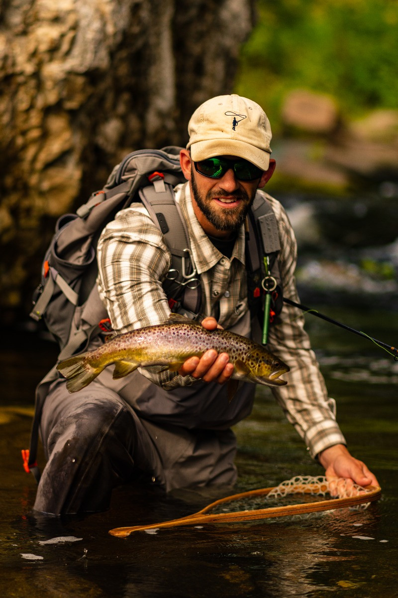 Brian Lansing holding a wild brown trout caught fly fishing.